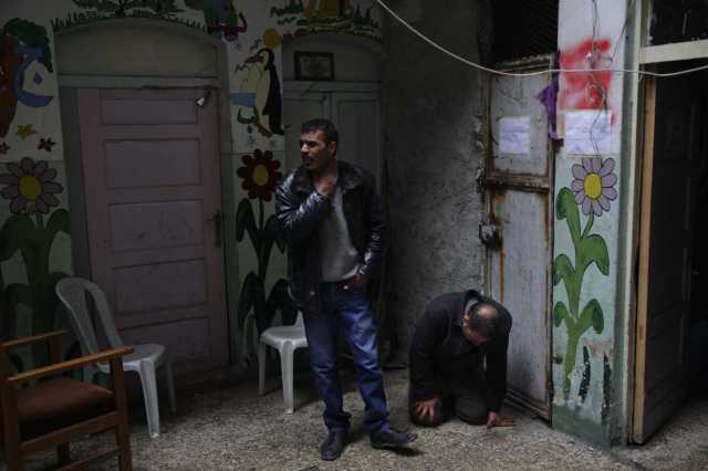 Two brothers mourn the loss of their father, Mohammed. Photo: Ben Solomon for the Guardian