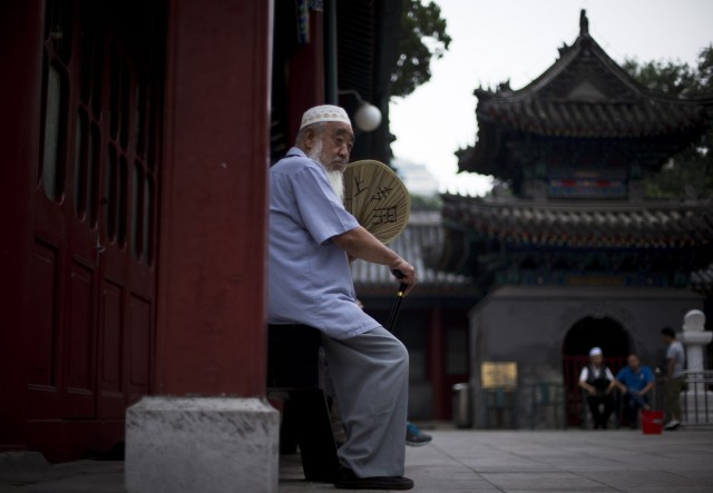 A Chinese Muslim man fans himself as he waits for the time to break his fast during the Muslim holy month of Ramadan at the Niujie mosque, the oldest and largest mosque in Beijing, China Wednesday, July 2, 2014. Students and civil servants in China's Muslim northwest, where Beijing is enforcing a security crackdown following deadly unrest, have been ordered to avoid taking part in traditional fasting during the Islamic holy month of Ramadan. (Andy Wong/Associated Press)